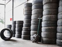 Used car tires stacked in piles at junkyard. Old wheels recycling and utilization concepr royalty free stock photo