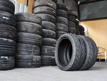 Used car tires stacked in piles at junkyard. Old wheels recycling and utilization concepr stock photography