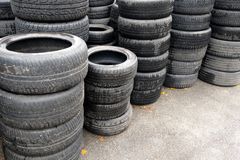 Used car tires stacked in piles at junkyard. Old wheels recycling and utilization.  Stock Images