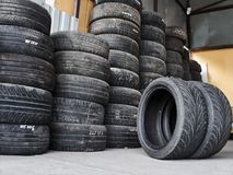 Used car tires stacked in piles at tire fitting service. Wheels for repair shop. Car service concepr royalty free stock image