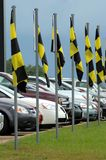Used Cars for Sale. Dealership decorates its car lot with yellow and black checked flags stock photography