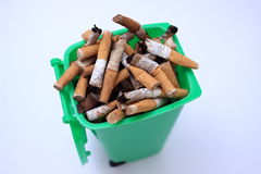 Used cigarette butts in green waste bin on white background. Green waste bin filled with cigarette butts on white background Stock Photo