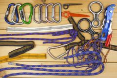 Used climbing gear on wooden background. Advertising boards of trade. The concept of extreme sports. Stock Photos