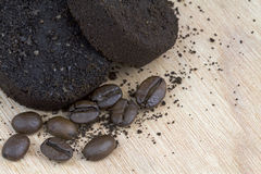 Used coffee grounds after espresso machine and coffee beans. On wooden background, macro image Stock Photo