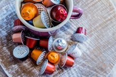 Coffe pods in enamel mug. Used coffee pods in enamel mugs against wooden background stock photos
