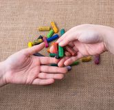 Used  color crayons and a teenagers hands. Used  color crayons and a hand giving out some Stock Images