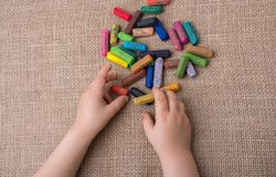 Used  color crayons and a toddlers hand. Holding one Stock Photo