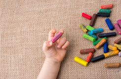 Used  color crayons and a toddlers hand. Holding one Stock Photos