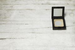 Used Compact pressed powder on white wooden background. Top view Stock Images
