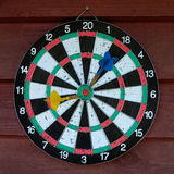 Used dartboard with two darts over wooden background. Royalty Free Stock Photos
