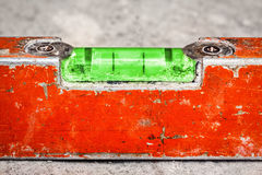 Used and dirty spirit level on a concrete wall. Macro image of a used and dirty spirit level on a concrete wall Royalty Free Stock Photos