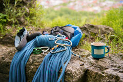 Used equipment for climbing where the rope carabiners and climbing slippers next to the mug on which an empty plate Royalty Free Stock Photo