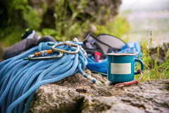 Used equipment for climbing where the rope carabiners and climbing slippers next to the mug on which an empty plate Stock Photos