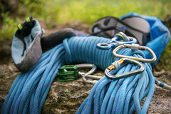 Used equipment for climbing where the rope carbines and climbing slippers lie on a rock Stock Image