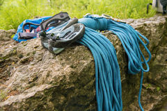 Used equipment for climbing where the rope carbines and climbing slippers lie on a rock. Close up Used equipment for climbing where the rope carbines and Royalty Free Stock Photo
