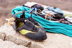 Used equipment for climbing where the rope carbines and climbing slippers lie on a rock Royalty Free Stock Images
