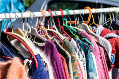 Used female sweaters on rack for reusing at flea market Stock Photography