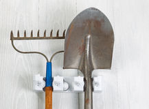 Used garden tools hanging from rack on white wooden boards Royalty Free Stock Images
