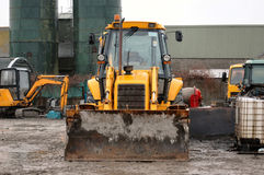 Used Heavy Plant. A muddy farmers yard with heavy plant machinery in the pouring rain Royalty Free Stock Photo