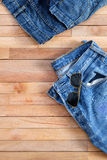 Used Jeans and Aviator sunglasses on top of wooden Royalty Free Stock Photography