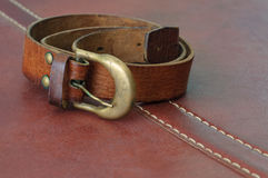 Used leather belt for men on brown leather background Royalty Free Stock Photo