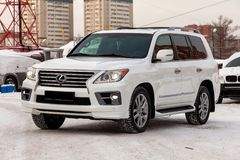 Used Lexus LX570 2013 year white pearl color with headlights on standing in the snow after presale preparation on a clear winter stock photos