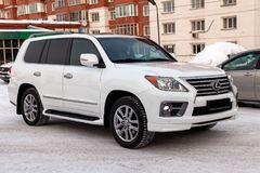 Used Lexus LX570 2013 year white pearl color with headlights on standing in the snow after presale preparation on a clear winter royalty free stock images