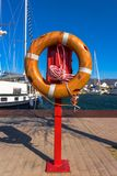 Used lifebuoy on a pole at the harbor in Roses, Spain. In the background sailboats and the beginning of the pyrenees  are visible Royalty Free Stock Image