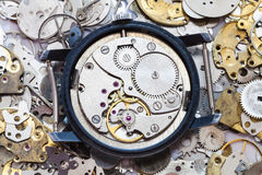 Used mechanical wristwatch on heap of spare parts Stock Photos