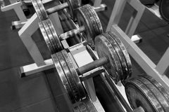 Used metal dumbbells on a rack in a gym. Sport and fitness equipment. royalty free stock photos