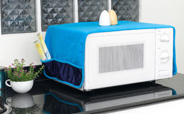 Microwave oven with the cover blanket to protect dust or dirty Royalty Free Stock Photo