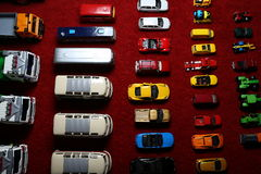 Used model cars from the top. Few rows and columns of the used colorful toy cars on the red carpet Royalty Free Stock Photo