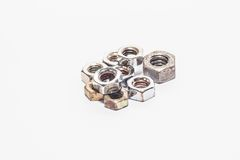 Used and new nuts for manufacturing and industry. With white background Royalty Free Stock Images