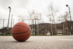 Used orange basketball with basket in background. Basketball street court. Terrain Stock Images