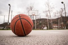 Used orange basketball with basket in background. Basketball street court. Terrain Stock Photos
