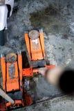 Used orange hydraulic floor jacks on concrete floor stock photography