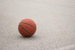 Used orange leather basketball on grey asphalt background. Leather ball for street basketball royalty free stock photos