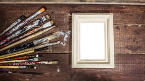 Used Paint brushes and photo frame Royalty Free Stock Photography