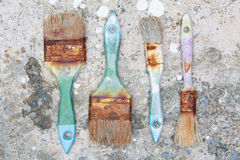 Used paint brushes. With size 63mm.(2-1/2 in) 25 mm(1 in) and 19mm.(3/4 in) on dirty floor Stock Photo