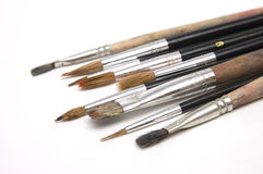 Used paint brushes on white. Bunch of used paint brushes on white background - diagonal composition Stock Image