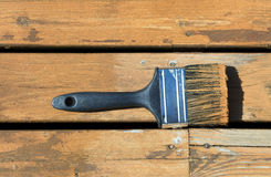 Used paintbrush filled with wood stain on a natural cedar deck. Used paintbrush filled with wood stain on a natural cedar wooden deck stock photos