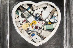 Used paintbrushes in black heart frame Stock Photography