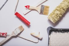 Used painting tools with red handles covered in warm white paint layed out in a composition on a plain white background Stock Photos