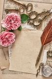 Used paper antique feather pen pink rose flowers. Used paper, antique feather pen, pink rose flowers. Vintage flat lay Royalty Free Stock Images