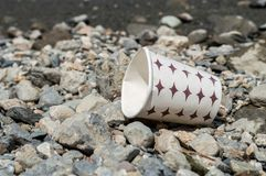 Used paper coffee mug dumped on the costal strip stock image