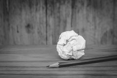 Used pencil with white crumpled paper ball put on wooden floor in black and white image. Business Creative and Idea Concept Used pencil with white crumpled Royalty Free Stock Photo