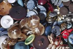 Used plastic buttons overview. Macro overview of mostly soft blue used colored plastic textiles garment plastic buttons pile.  textiles garments components Royalty Free Stock Photos