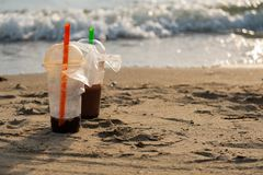 Used plastic cups on beach stock images