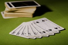 Used playing cards on green carpet Stock Images