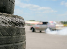 Used racing tires. With sport car on background Royalty Free Stock Images
